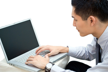 Asian business male looking at laptop